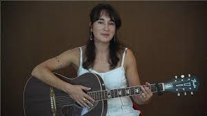Michelle Shocked met gitaar en lang haar